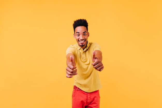 Homem jovem confiante olhando para a direita e mostrando os polegares. foto interna de cara elegante e entusiasmado.