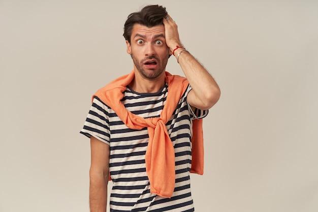 Homem jovem confuso e atordoado com cerdas em uma camiseta listrada e suéter nos ombros mantém a mão na cabeça e a boca aberta