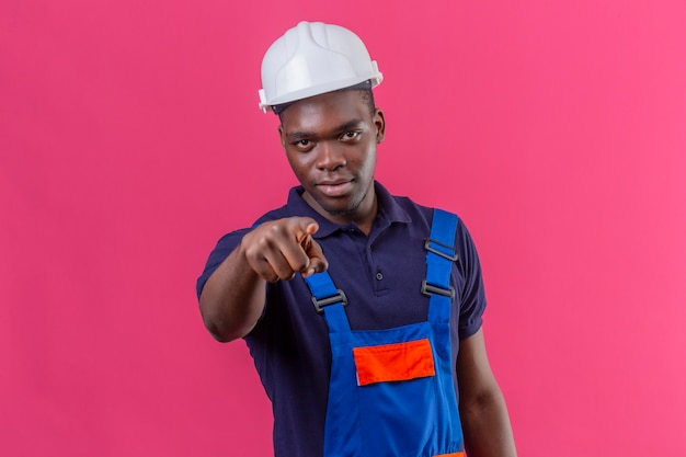 Homem jovem construtor afro-americano descontente com uniforme de construção e capacete de segurança apontando o dedo com expressão séria no rosto em pé na rosa