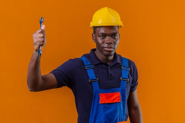Homem jovem construtor afro-americano descontente com uniforme de construção e capacete de segurança, segurando a chave inglesa com a mão levantada e expressão de raiva em pé na laranja