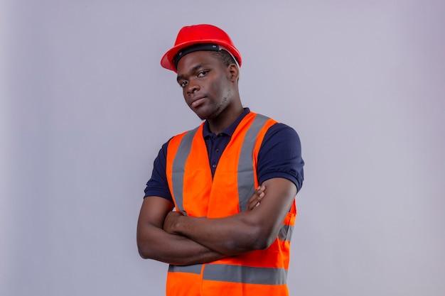 Homem jovem construtor afro-americano usando colete de construção e capacete de segurança em pé com os braços cruzados, parecendo suspeito