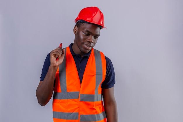 Homem jovem construtor afro-americano usando colete de construção e capacete de segurança segurando uma chave ajustável, olhando para o lado com um sorriso no rosto de pé