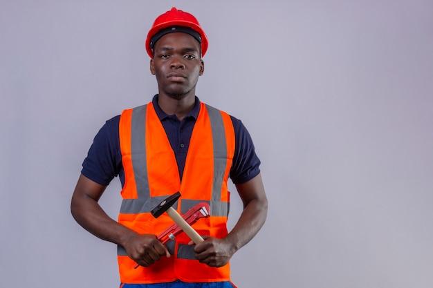 Homem jovem construtor afro-americano usando colete de construção e capacete de segurança, segurando uma chave inglesa ajustável e um martelo em forma de cruz, com o rosto sério em pé