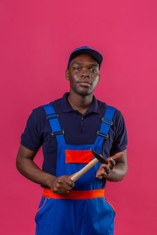 Homem jovem construtor afro-americano usando uniforme de construção e boné segurando um martelo nas mãos, parecendo confiante em pé na rosa
