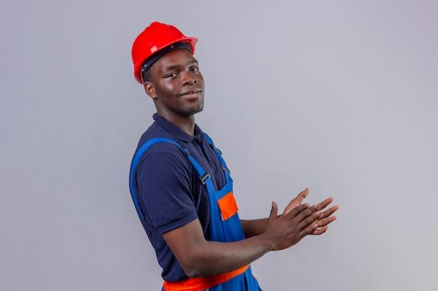 Homem jovem construtor afro-americano usando uniforme de construção e capacete de segurança, aplaudindo com um sorriso no rosto em pé