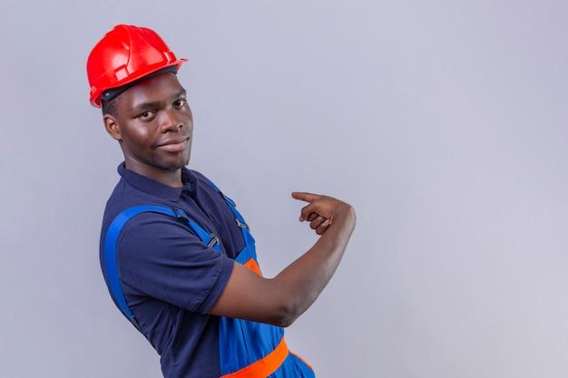 Homem jovem construtor afro-americano usando uniforme de construção e capacete de segurança apontando para trás com o dedo indicador com um sorriso confiante no rosto em pé