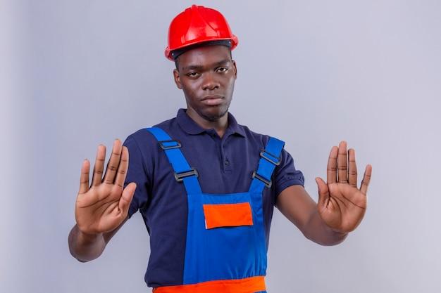 Homem jovem construtor afro-americano usando uniforme de construção e capacete de segurança em pé com as mãos abertas, fazendo sinal de pare com expressão séria e confiante gesto de defesa em pé