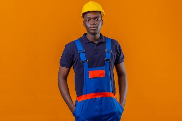Homem jovem construtor afro-americano usando uniforme de construção e capacete de segurança em pé com as mãos nos bolsos com expressão séria e confiante em laranja isolada