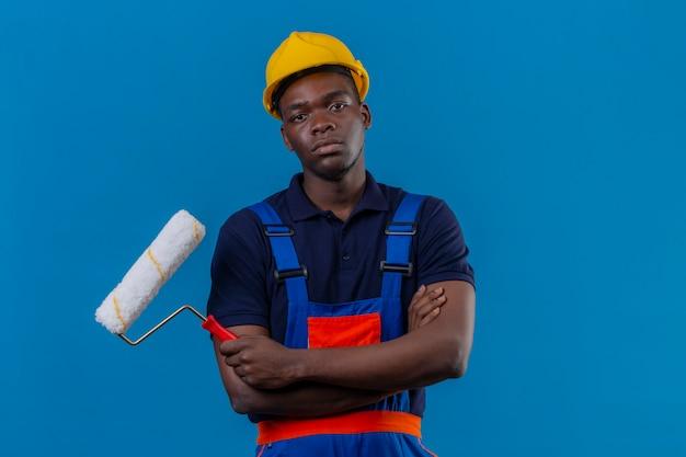 Homem jovem construtor afro-americano usando uniforme de construção e capacete de segurança em pé com os braços cruzados no peito, segurando o rolo de pintura com o rosto carrancudo descontente