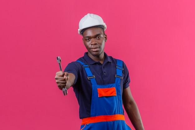Homem jovem construtor afro-americano usando uniforme de construção e capacete de segurança, mostrando a chave inglesa com uma expressão séria e confiante em pé na rosa