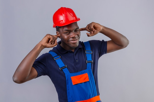 Homem jovem construtor afro-americano usando uniforme de construção e capacete de segurança, orelhas em forma de cone com os dedos e uma expressão irritada pelo barulho de sons altos em pé