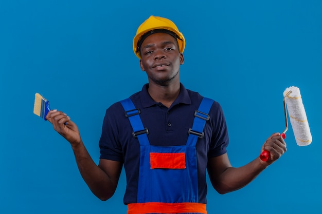 Homem jovem construtor afro-americano usando uniforme de construção e capacete de segurança, segurando o pincel e o rolo de pintura, sorrindo amigável em pé no azul