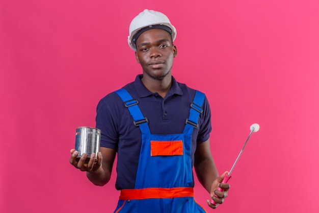 Homem jovem construtor afro-americano usando uniforme de construção e capacete de segurança segurando uma lata de tinta e um rolo com expressão séria e confiante em pé na rosa