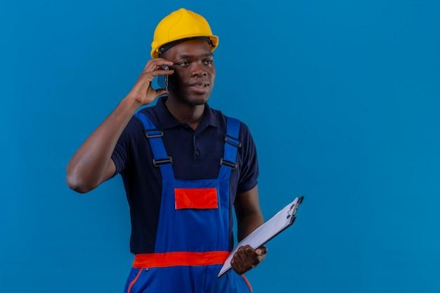 Homem jovem construtor afro-americano usando uniforme de construção e capacete de segurança segurando uma prancheta, falando no celular, sorrindo em pé sobre azul