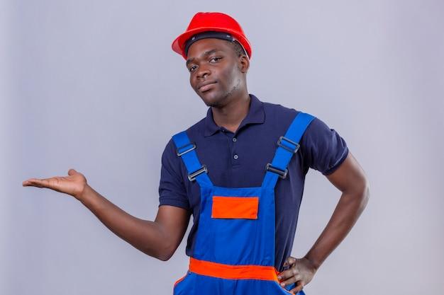 Homem jovem construtor afro-americano usando uniforme de construção e capacete de segurança, sorrindo amigável, apresentando e apontando com a palma da mão em pé