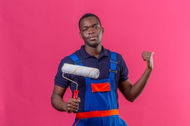 Homem jovem construtor afro-americano usando uniforme de construção segurando o rolo de pintura apontando para trás com o polegar, parecendo confiante em pé na rosa
