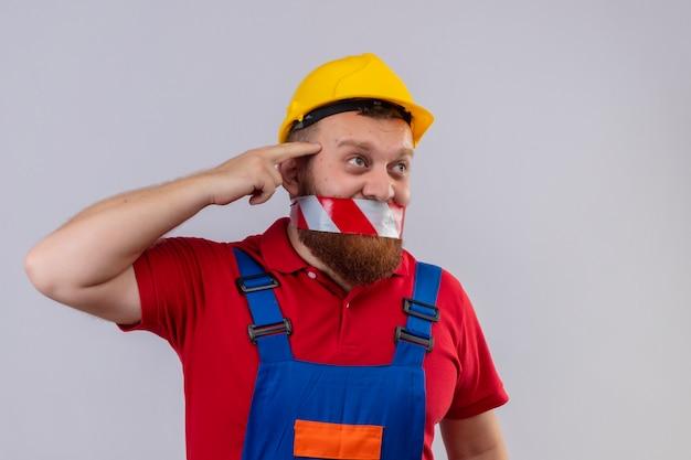Homem jovem construtor barbudo com uniforme de construção e capacete de segurança com fita adesiva sobre a boca, olhando de lado confuso apontando para a têmpora