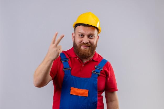 Homem jovem construtor barbudo com uniforme de construção e capacete de segurança olhando para a câmera sorrindo aparecendo e apontando para cima com os dedos número dois ou sinal de vitória