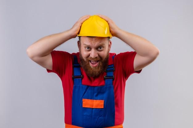 Homem jovem construtor barbudo em uniforme de construção e capacete de segurança olhando para a câmera estressado e confuso tocando sua cabeça gritando