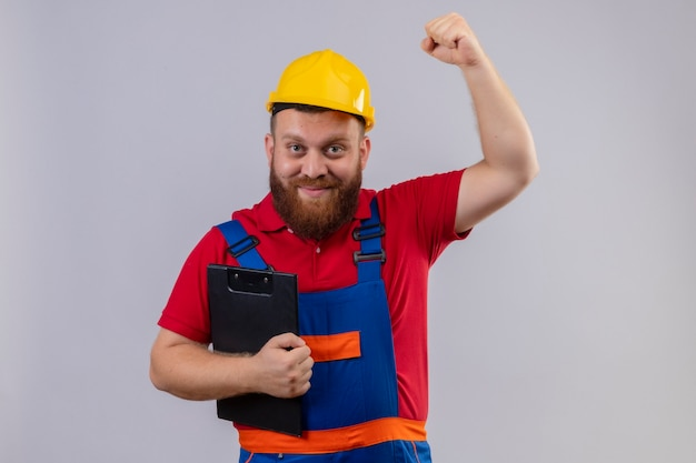 Homem jovem construtor barbudo em uniforme de construção e capacete de segurança segurando a prancheta, levantando o punho positivo e feliz, conceito vencedor