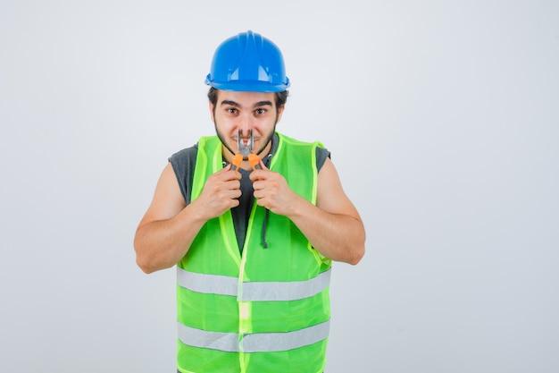 Homem jovem construtor beliscando o nariz com um alicate em uniforme de trabalho e parecendo engraçado. vista frontal.