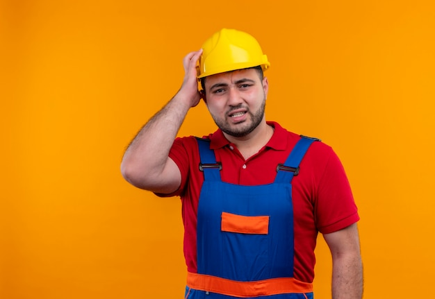 Homem jovem construtor com uniforme de construção e capacete de segurança olhando para a câmera descontente com a mão na cabeça por engano e parecendo confuso