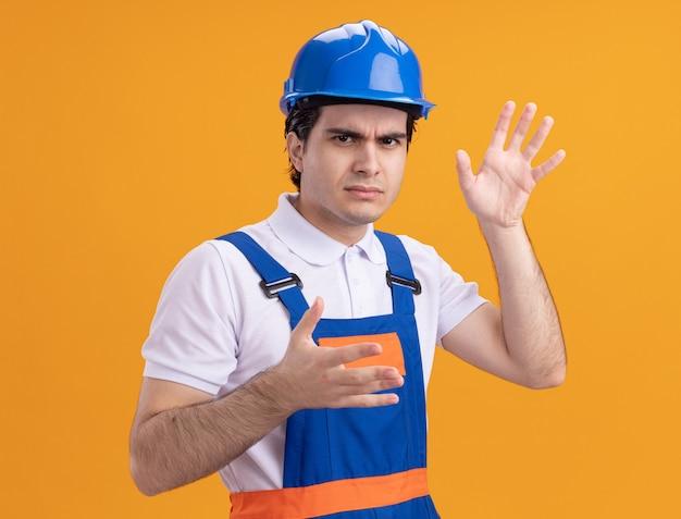 Homem jovem construtor com uniforme de construção e capacete de segurança olhando para a frente e ficando insatisfeito com os braços estendidos em pé sobre a parede laranja