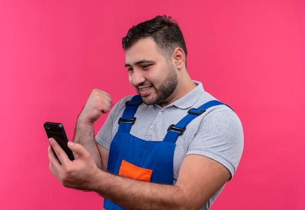 Homem jovem construtor com uniforme de construção segurando o punho cerrado de smartphone feliz e animado