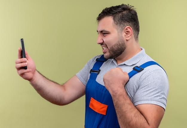 Homem jovem construtor com uniforme de construção segurando um smartphone olhando para uma tela se passando por um vencedor com o punho cerrado feliz e animado