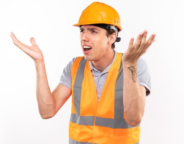 Homem jovem construtor confuso em uniforme espalhando as mãos isoladas na parede branca