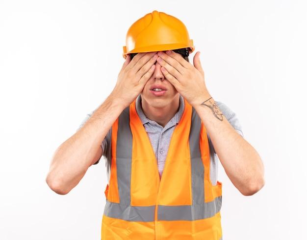 Homem jovem construtor de uniforme coberto com os olhos e as mãos isoladas na parede branca