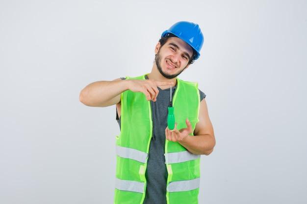 Homem jovem construtor de uniforme, mostrando o sinal do tamanho com uma chave de fenda e olhando feliz, vista frontal.