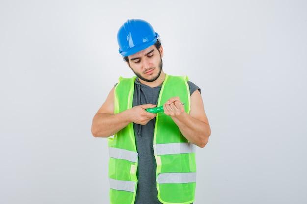Homem jovem construtor de uniforme, olhando para a chave de fenda e olhando pensativo, vista frontal.