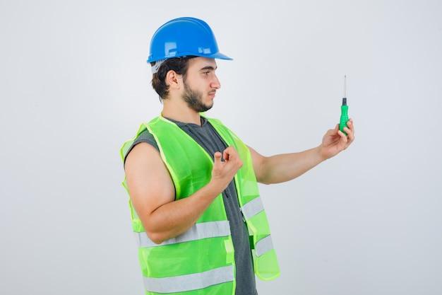 Homem jovem construtor de uniforme, segurando a chave de fenda enquanto aponta o polegar para a câmera e parece confiante, vista frontal.