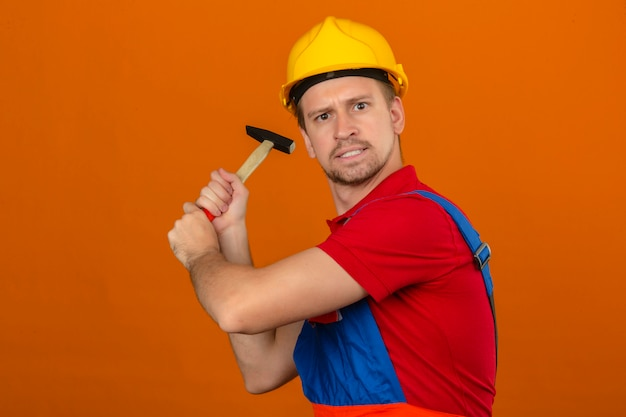 Homem jovem construtor em uniforme de construção e capacete de segurança com expressão de raiva, ameaçando bater com martelo sobre parede laranja isolada