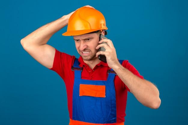 Homem jovem construtor em uniforme de construção e capacete de segurança, falando no telefone móvel infeliz em estresse ao longo da parede isolada azul