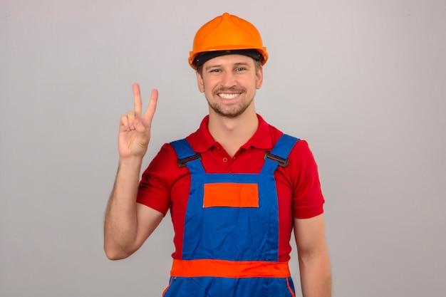 Homem jovem construtor em uniforme de construção e capacete de segurança, mostrando e apontando para cima com os dedos número dois ou sinal de vitória enquanto sorrindo confiante e feliz sobre parede branca isolada