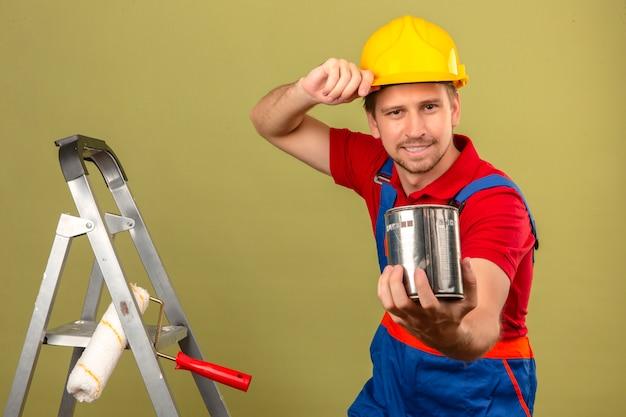 Homem jovem construtor em uniforme de construção e capacete de segurança na escada de metal, segurando a pintura pode apresentar a câmera sobre parede verde isolada