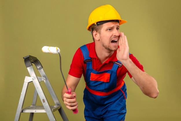 Homem jovem construtor em uniforme de construção e capacete de segurança na escada de metal segurando o rolo de pintura e gritando com raiva em voz alta com a mão na boca sobre parede verde isolada