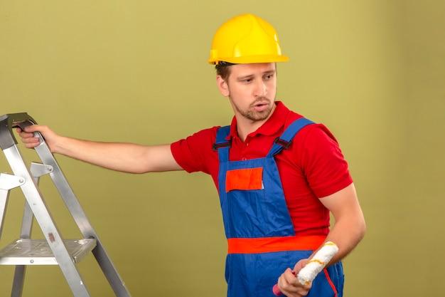 Homem jovem construtor em uniforme de construção e capacete de segurança na escada de metal segurando o rolo de pintura, olhando de soslaio sobre parede verde isolada