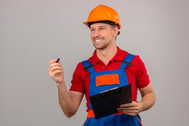 Homem jovem construtor em uniforme de construção e capacete de segurança segurando a área de transferência e caneta, olhando para o lado com sorriso no rosto sobre parede branca isolada