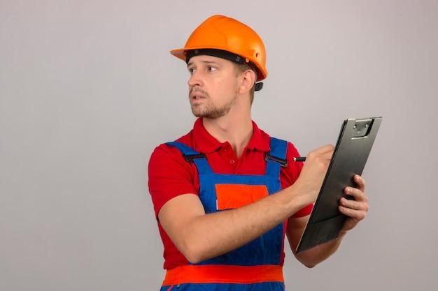 Homem jovem construtor em uniforme de construção e capacete de segurança segurando a área de transferência e olhando para longe sobre parede branca isolada