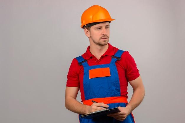 Homem jovem construtor em uniforme de construção e capacete de segurança segurando a área de transferência e olhando para o lado com cara séria sobre parede branca isolada