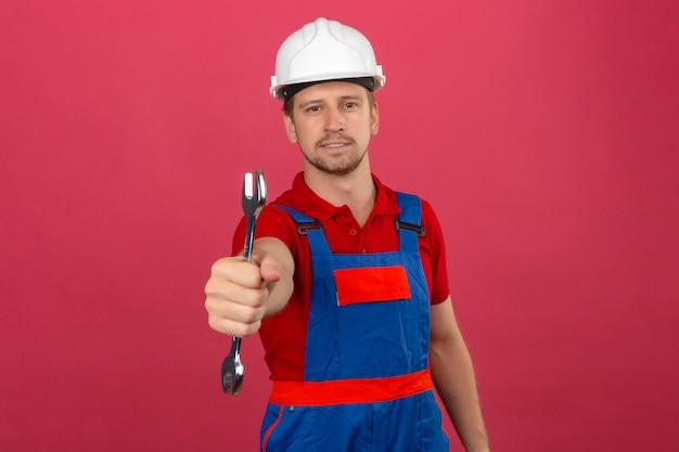 Homem jovem construtor em uniforme de construção e capacete de segurança, segurando a chave em uma mão, levantando o braço sobre parede rosa isolada