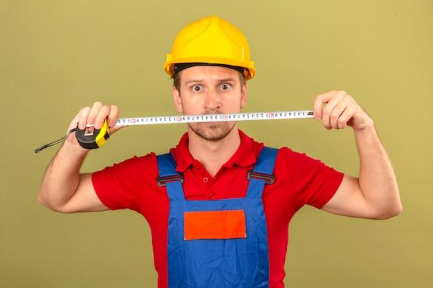 Homem jovem construtor em uniforme de construção e capacete de segurança segurando a fita-linha com rosto surpreso sobre parede verde isolada