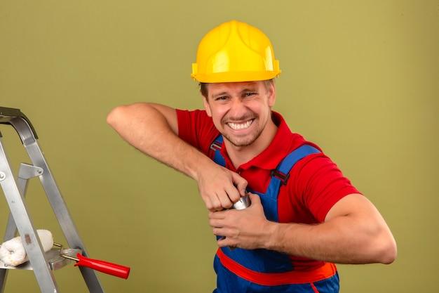 Homem jovem construtor em uniforme de construção e capacete de segurança, tentando abrir a pintura pode dificilmente abrir o conceito sobre parede verde isolada