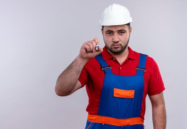 Homem jovem construtor em uniforme de construção e capacete de segurança tentando escrever no ar com uma caneta, olhando com uma cara séria