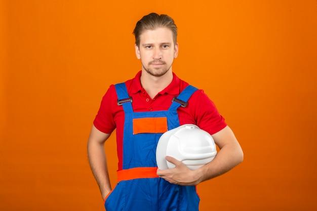Homem jovem construtor em uniforme de construção, segurando o capacete de segurança na mão com sorriso confiante no rosto em pé sobre a parede laranja isolada