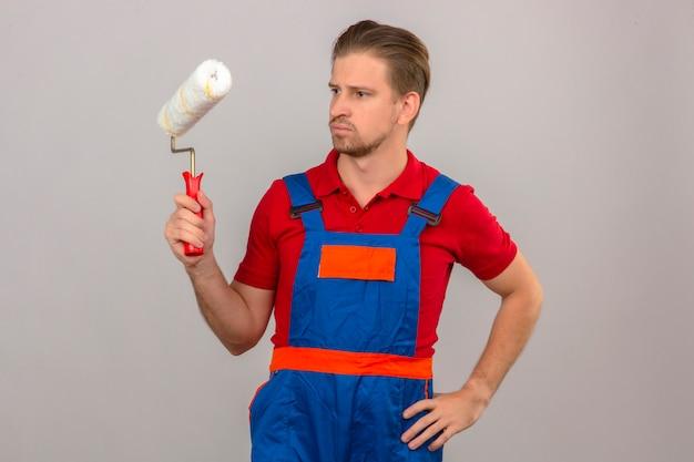 Homem jovem construtor em uniforme de construção segurando o rolo de pintura e olhando para ele com expressão de rosto cético sobre parede branca isolada