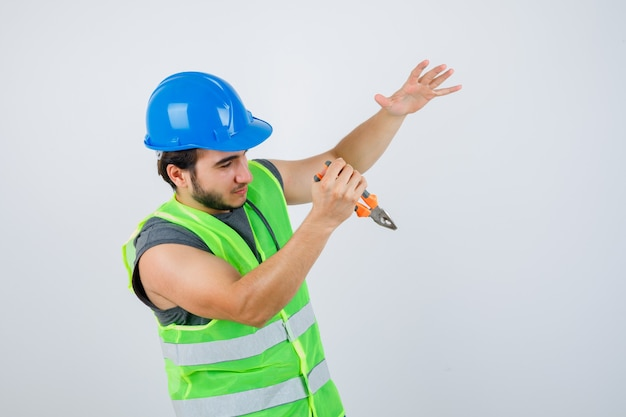 Homem jovem construtor em uniforme de trabalho, segurando um alicate enquanto finge pegar algo e parece autoconfiante, vista frontal.
